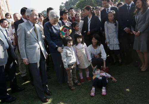 Japan's Emperor Akihito and Empress Michiko pose for a picture with children during their visit to the Lodhi garden in New Delhi