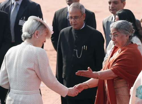 Japan's Empress Michiko shakes hands with Kaur, wife of India's Prime Minister Singh as India's President Mukherjee looks on at the forecourt of India's presidential palace Rashtrapati Bhavan in New Dehli