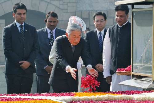 Japan's Emperor Akihito scatters rose petals at the Mahatma Gandhi memorial at Rajghat in New Delhi
